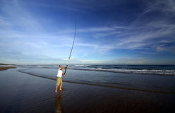 Fishing. Young fisher man alone on a beach Royalty Free Stock Photo