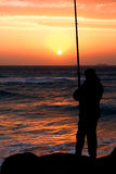Fishing. A man fishing on beach at sunrise near a pier in early morning with sun lights reflect on ocean water and rock Stock Images