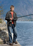 Fishing. The young man fishes in a gulf on a spinning royalty free stock images