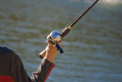 Fishing. Person holding a fishing rod and reel near a lake Royalty Free Stock Image