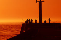 Fishing. Men fishing for fish in the sea port at sunset Royalty Free Stock Photography