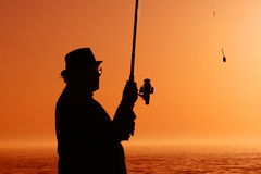 Fishing. Man in a hat and a fishing rod - fishing Royalty Free Stock Photography
