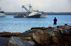 Fishing. Man fishing on rocks with fishing boats in the background Stock Images