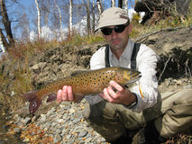 Fishing. Trout catched on wild river Royalty Free Stock Images