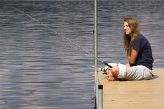 Fishing. Pretty teenage girl sits on a dock fishing Stock Photography