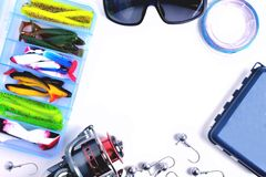 Fishing accessories, box with silicone baits, fishing glasses, accessory box, fishing reel, hooks, braided fishing line on a white royalty free stock photos