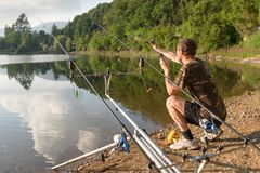 Fishing adventures, carp fishing. Angler with camouflage t-shirt is feeding fishes throwing boilies with a slingshot. Carp fishing. Fisherman on the shore of a royalty free stock photography