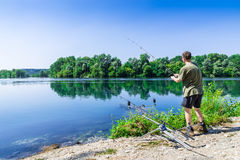 Fishing adventures, carp fishing. Angler is fishing with carpfishing technique in freshwater. Fisherman in a beautiful summer day with light blue sky stock photo