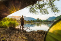 Fishing adventures, carp fishing. Angler, at sunset, is fishing with carpfishing technique. Fisherman in backlight. Camping on the shore of the lake on a stock image