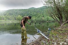Fishing adventures, carp fishing. Fisherman with green rubber boots royalty free stock image