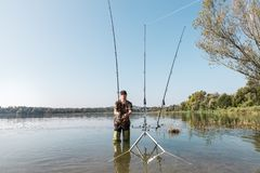 Fishing adventures, carp fishing. Fisherman with green rubber boots. Fisherman with green rubber boots and camouflage clothing is in the water with a fishing rod royalty free stock images