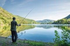Fishing adventures. Fisherman on the lake shore Stock Photo