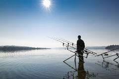 Fishing adventures. Fisherman near the carpfishing equipment Royalty Free Stock Photography