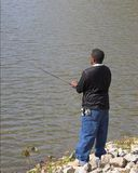 Fishing Alone. Lone African American teenager looking to hook a fish for dinner Royalty Free Stock Photos
