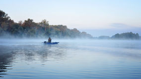 Fishing. Angler fishing early in the morning on the misty river. Dnipro river. Ukraine. Early autumn Stock Photos