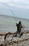 Fishing anglers catch big fish. Two anglers reel in big fish. fishing from beach in the ocean or sea on a windy day stock photos