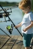 Fishing, angling, activity, adventure, sport. Child with fishing rod on wooden pier. Summer vacation, hobby, lifestyle. Little boy learn to catch fish in lake stock image