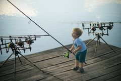 Fishing, angling, activity, adventure, sport. Little boy learn to catch fish in lake or river. Summer vacation, hobby, lifestyle. Child with fishing rod on royalty free stock photo