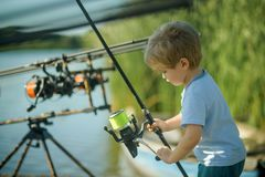 Fishing, angling, activity, adventure, sport. Little boy learn to catch fish in lake or river. Summer vacation, hobby, lifestyle. Childhood, education stock photo