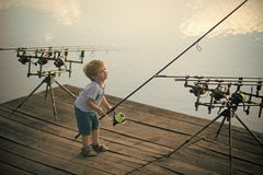 Fishing, angling, activity, adventure, sport. Little boy learn to catch fish in lake or river. Summer vacation, hobby, lifestyle. Child with fishing rod on stock image