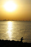 Fishing on arabian gulf. Silhouette of man Fishing on arabian gulf at sunset royalty free stock image
