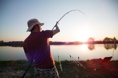Fishing as recreation and sports displayed by fisherman at lake. During sunset Stock Photography