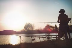 Fishing as recreation and sports displayed by fisherman at lake. During sunset Stock Photo