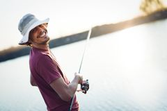 Fishing as recreation and sports displayed by fisherman at lake. During sunset Royalty Free Stock Image