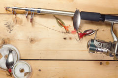 Fishing background with angling equipment on the wooden surface Royalty Free Stock Photography