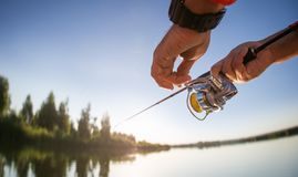 Fisherman with spinning on the lake. royalty free stock photo