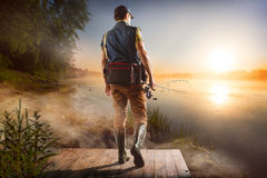 Fishing background. Young man fishing at misty sunrise Stock Photography