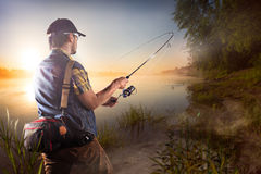 Fishing background. Young man fishing at misty sunrise Stock Photos