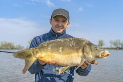 Fishing backgrounds. Fisherman with carp fish in hands.  royalty free stock image