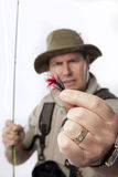 Fishing bait. Fly fisherman holding out his favourite bait toward camera on white background Stock Photos