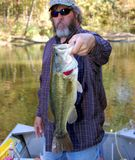 Fishing for bass. Fisherman holding a large mouth bass closeup Royalty Free Stock Photo