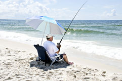 Fishing from the Beach. A man sitting in a beach chair with his fishing pole fishing in the ocean with a blue stripped umbrella shielding him from the sun Stock Photos