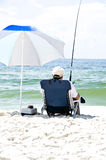 Fishing from the Beach. Man fishing from the beach sitting in a beach chair holding a fishing pole and being shaded with an umbrella Royalty Free Stock Photos