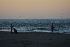 Fishing on beach at dusk Stock Photo