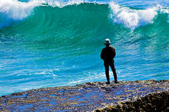 Fishing In Big Water. A man standing on a rock, fishing in the surf royalty free stock images