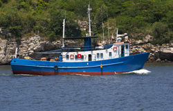 Fishing boat. In a rocky bay Stock Photography
