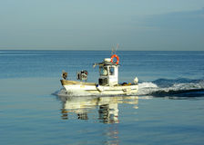 Fishing boat. Little fishing boat over flat sea Stock Photos
