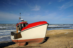 Fishing boat. Windy day at the beach with a fishing boat Royalty Free Stock Image