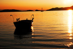 boat at sunset. A fishing boat in the water at sunset time. Greece Royalty Free Stock Photos