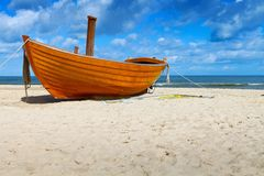 Fishing Boat. Wooden fishing boat on a sandy beach in sunny day Stock Photo