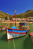 Fishing boat. A colorful painted fishing boat swimming in the water and docking at the harbor in False Bay, South Africa, in front of little houses close to the Royalty Free Stock Photo
