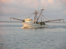 Fishing boat. Old worn fishing boat sailing out in the morning sun Stock Images