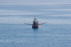 Fishing Boat. A trawler with gear out fishing on an empty ocean Stock Photo