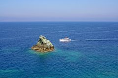 A fishing boat in the Aegean Sea. Fishermen in the boat in the morning, against a rock of volcanic rock and the Aegean Sea royalty free stock photography