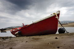 Fishing boat alone in the sand. A red and old fishing boat stranded in the sand of a beach near a little fishing rural village Royalty Free Stock Photo