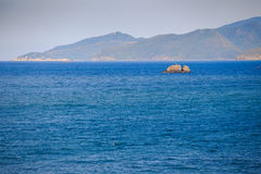 fishing boat amidst azure sea against hilly tropical island Royalty Free Stock Images